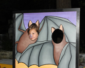 A photo of a child in a bat cutout photo op