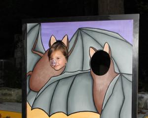 A photo of a child in a bat cutout photo op
