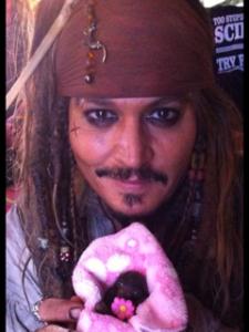 A photograph of Johnny Depp holding an orphaned fruit bat named Jacki Sparrow